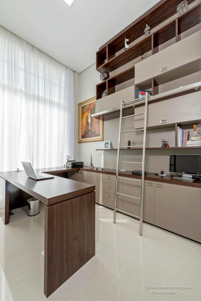 O projeto combina mesas e prateleiras em acabamento amadeirado com gavetas e nichos em tons nudes. Atrás da mesa do computador, fica uma escada, que facilita o acesso às prateleiras e nichos mais altos do móvel.