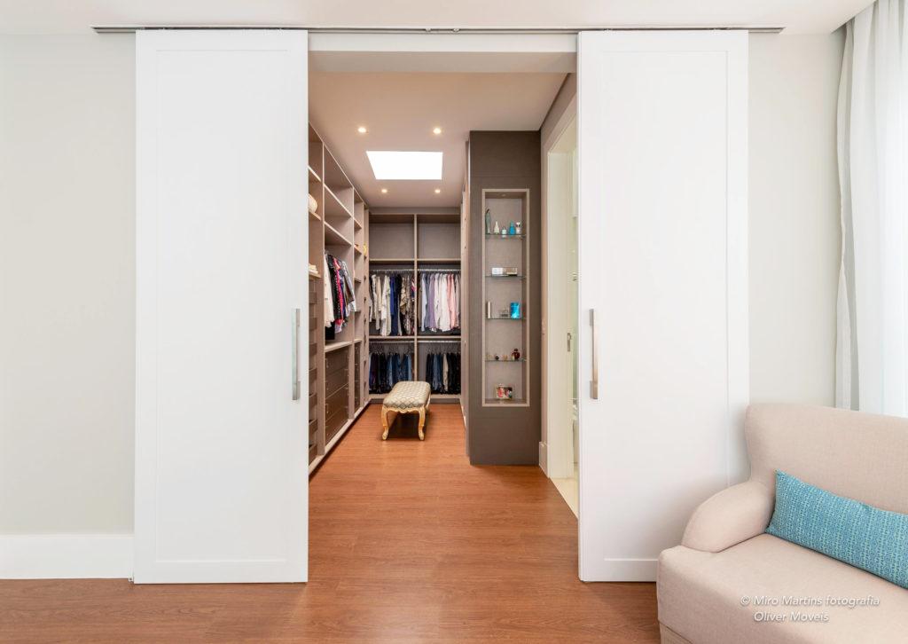 Closet com portas entreabertas. Acabamentos externos em tons claros e interior do closet em tom amadeirado com prateleiras e um banco central. Através das portas se vê as roupas penduras.