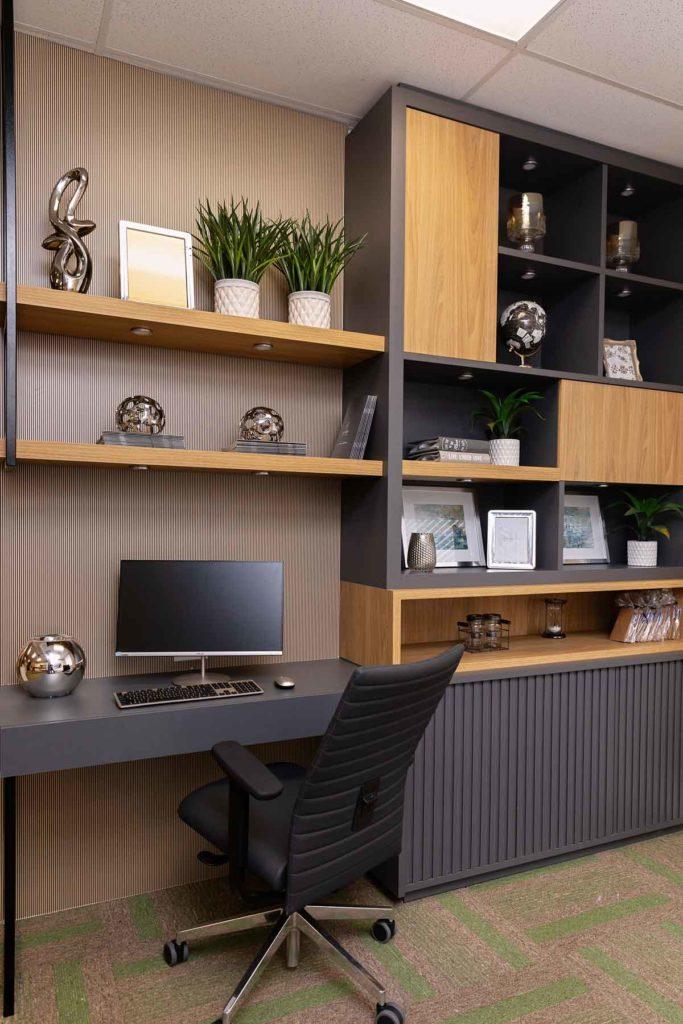 Este projeto de Home Office possui uma mesa embutida ao armário e prateleiras. A mesa do computador possui acabamento em tom preto, sobreposta por prateleiras de madeira natural. O móvel está decorado com peças de metal, vasos de plantas, porta-retratos e livros.